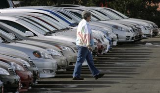 A prospective buyer searches through long lines of unsold Corolla and Camry sedans at a Toyota dealership in Boulder, Colo., in 2007. (AP Photo/David Zalubowski)