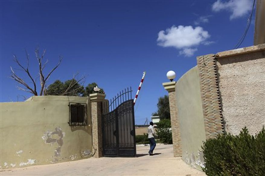 On Sunday, Sept. 16, 2012, a man walks near the gate of a safe house that was raided by attackers following the Sept. 11 assault on the U.S. Consulate in Benghazi, Libya, in which four Americans were killed, including Ambassador J. Christopher Stevens. (AP Photo/Mohammad Hannon)