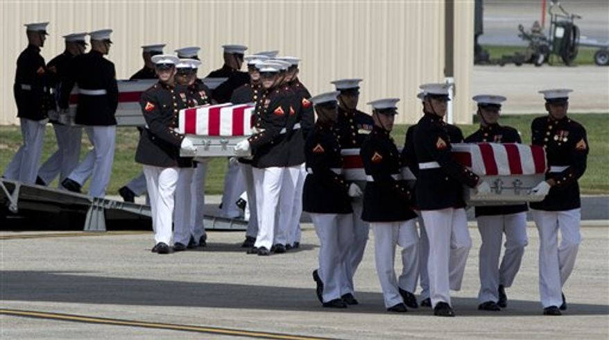 Carry teams move flag-draped transfer cases containing the remains of Americans killed in Benghazi, Libya, from a transport plane during a Transfer of Remains Ceremony on Friday, Sept. 14, 2012, at Andrews Air Force Base in suburban Washington. (AP Photo/Carolyn Kaster)