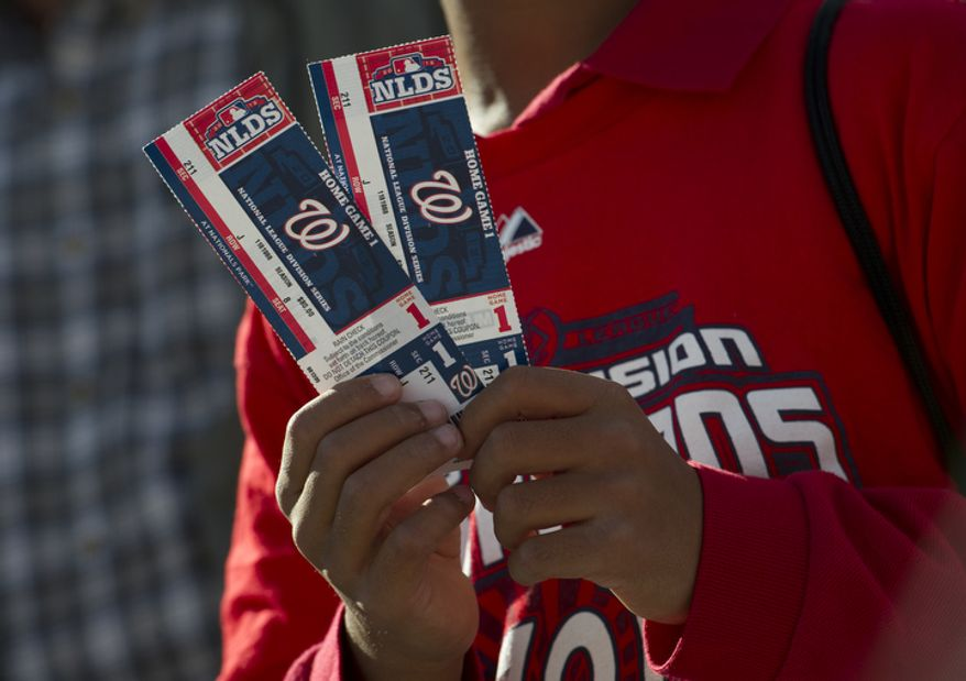 A young fan holds up his tickets for the Nationals' first home playoff game at Nationals Park on Wednesday, Oct. 10, 2012. (Barbara L. Salisbury/The Washington Times)