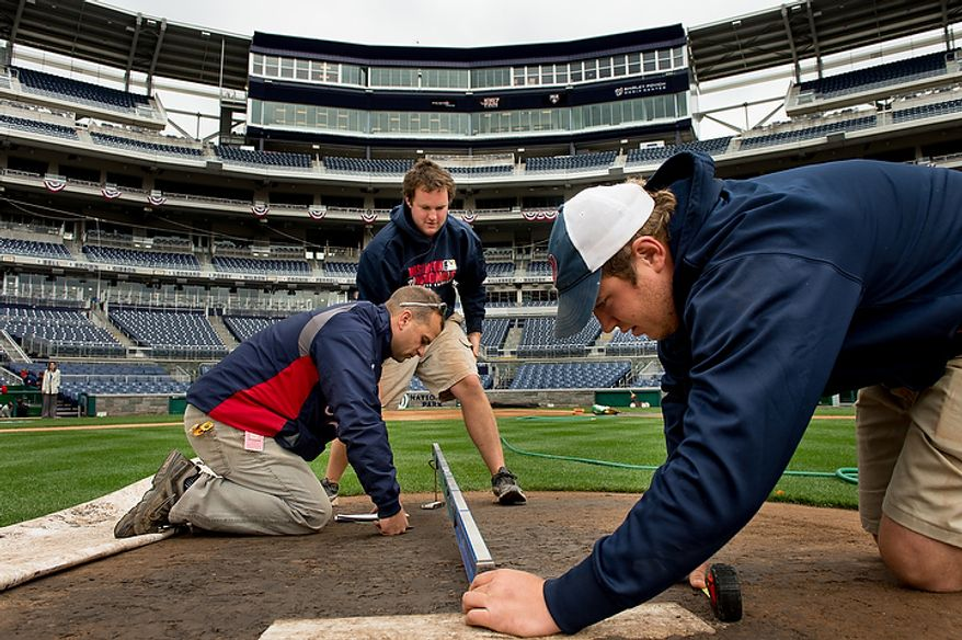 Head groundskeeper John Turnour (from left), assistant groundskeeper Matt Coates and Marty Guetting with the grounds crew conduct measurements for the pitching mound as they get ready for game three at Nationals Park as the Washington Nationals take on the St. Louis Cardinals in the first round of the Major League Baseball playoffs in Washington on Monday, Oct. 8, 2012. (Andrew Harnik/The Washington Times)