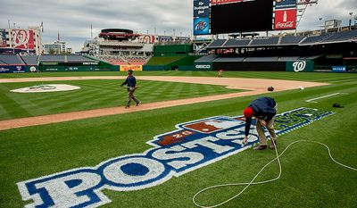 Assistant head groundskeeper Mike Hrivnak airbrushes a post-season logo behind the base path between home plate and first base as he and the grounds crew get ready for game three at Nationals Park, where the Washington Nationals will take on the St. Louis Cardinals in the first round of the Major League Baseball playoffs, in Washington on Monday, Oct. 8, 2012. (Andrew Harnik/The Washington Times)