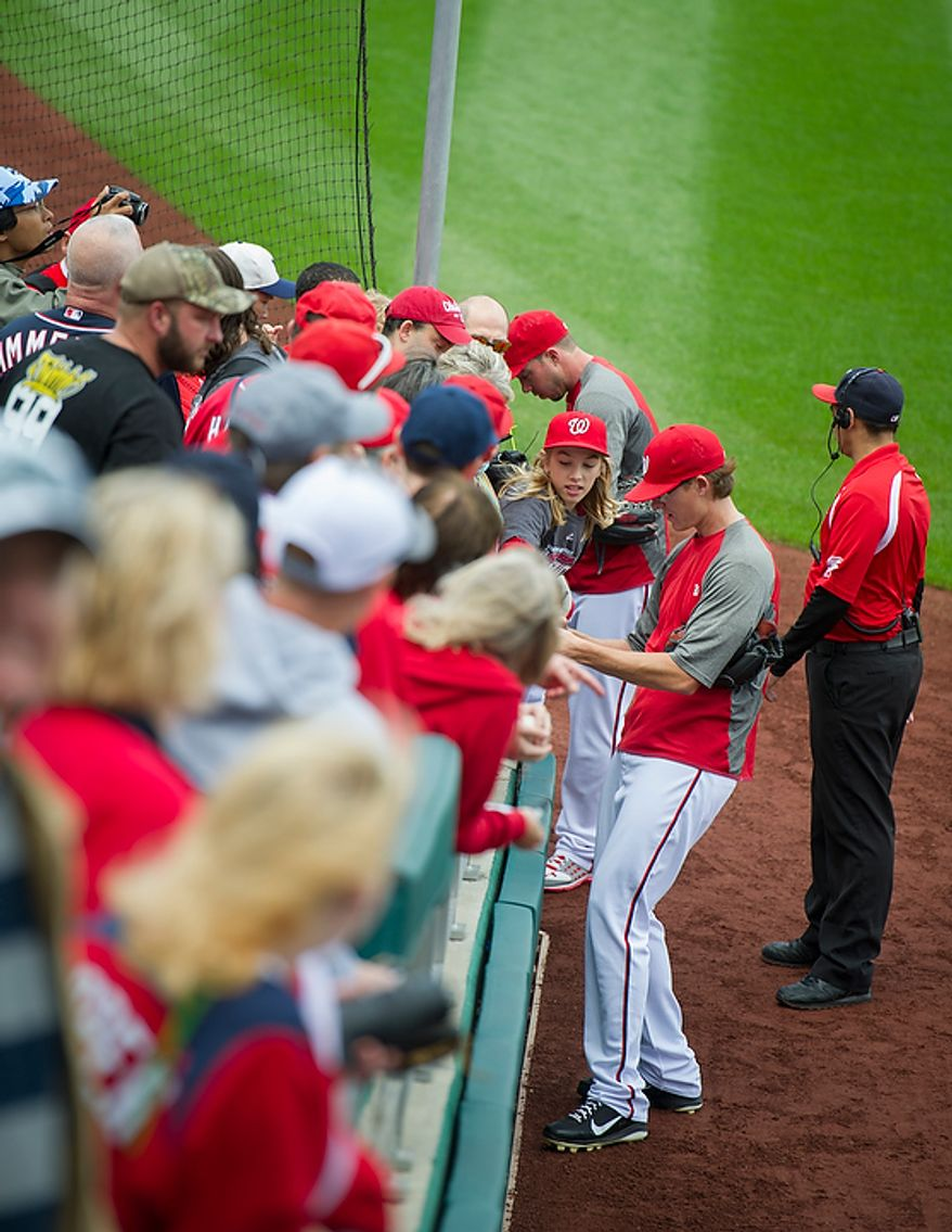 Washington Nationals player Tyler Clippard signs autographs before the Nats host the St. Louis Cardinals for game three of the National League Division Series at Nationals Park in Washington on Wednesday, Oct. 10, 2012. (Rod Lamkey Jr./The Washington Times)