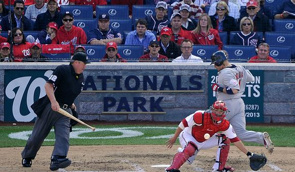 St. Louis Cardinals catcher Yadier Molina (R) scores before the ball gets to Washington Nationals catcher Kurt Suzuki in the top of the 6th inning of Game 3 of the National League Division Series at Nationals Park, Washington, D.C.., Oct. 10, 2012. (Preston Keres/Special to The Washington Times)