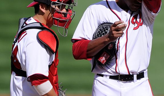 Washington Nationals catcher Kurt Suzuki (24) visits with starting pitcher Edwin Jackson (33) after giving up three runs in the second inning of Game 3 of the National League Division Series at Nationals Park, Washington, D.C., Oct. 10, 2012. (Preston Keres/Special to The Washington Times)