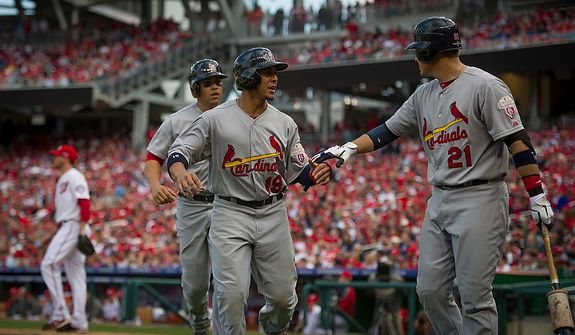 Cardinals' Jon Jay (19) and Carlos Beltran (3) are greeted at the dugout by Allen Craig (21) after scoring on a two-run RBI single by Matt Holliday in the top of the eighth inning as the Washington Nationals host the St. Louis Cardinals for Game 3 of the National League Division Series at Nationals Park in Washington, D.C., Wednesday, Oct. 10, 2012. (Rod Lamkey Jr./The Washington Times)