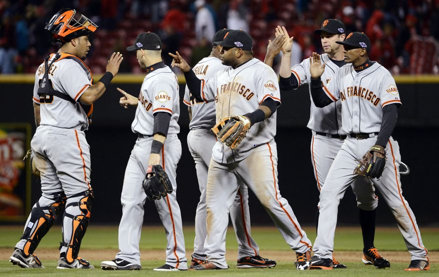 San Francisco Giants players celebrate after defeating the Cincinnati Reds 8-3 in Game 4 of the National League division baseball series, Wednesday, Oct. 10, 2012, in Cincinnati. (AP Photo/Michael Keating)