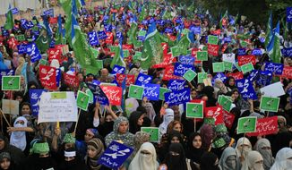 "Supporters of Pakistani religious party Jamaat-e-Islami hold up placards during a Oct. 7, 2012, rally in Lahore, Pakistan, against a film insulting the Prophet Muhammad. Most placards read, ""Muhammad, may God pray on him and grant him peace."" (Associated Press)"