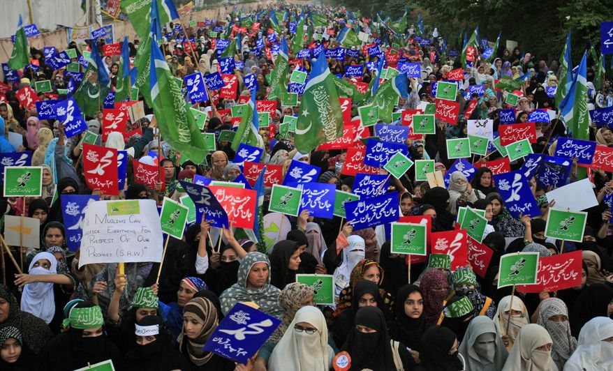 """Supporters of Pakistani religious party Jamaat-e-Islami hold up placards during a Oct. 7, 2012, rally in Lahore, Pakistan, against a film insulting the Prophet Muhammad. Most placards read, """"Muhammad, may God pray on him and grant him peace."""" (Associated Press)"""