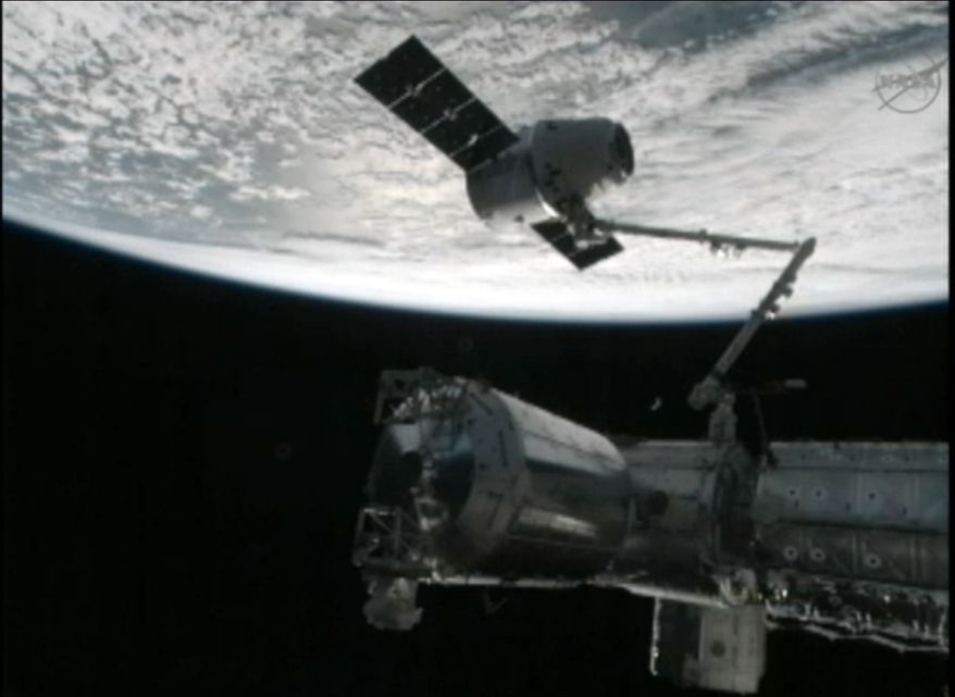 A robot arm on the International Space Station captures the Dragon capsule as they pass over the South Atlantic Ocean early Wednesday, Oct. 10, 2012. It's the first official delivery by the California-based SpaceX company under a $1.6 billion contract with NASA. The contract calls for 12 such shipments. (AP Photo/NASA)