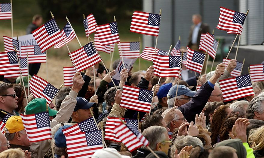 Supporters wave flags during Republican Mitt Romney's campaign stop on Oct. 9, 2012, in Van Meter, Iowa. (AP Photo/Charlie Neibergall)