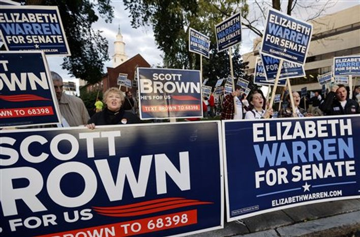 Supporters of Republican incumbent Sen. Scott Brown and Democratic challenger Elizabeth Warren hold signs outside Symphony Hall in Springfield, Mass., Wednesday Oct. 10, 2012, prior to their third debate. (AP Photo/Elise Amendola)