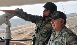 Turkish Chief of Staff Gen. Necdet Ozel (right) listens Oct. 9, 2012, to a commander during his tour of the military along the border with Syria in Hatay, Turkey. (Associated Press/Turkish Military)