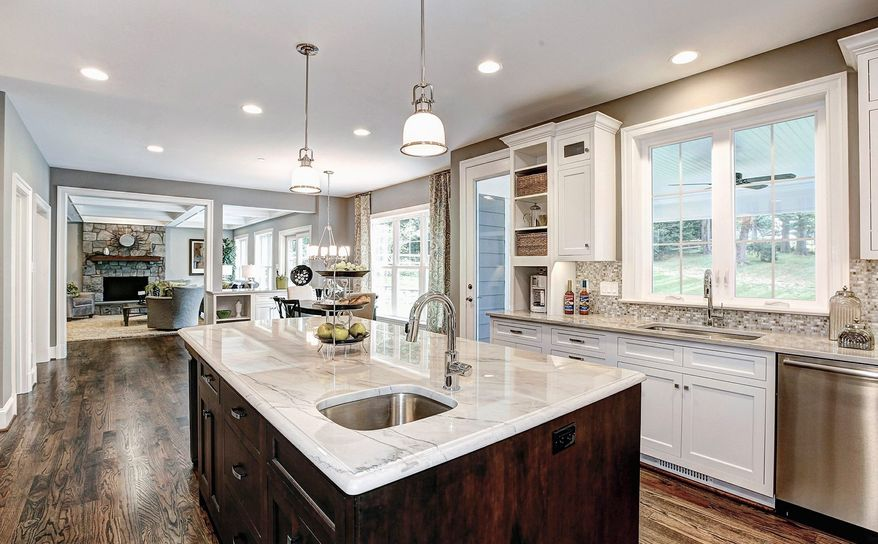 The center-island kitchen has granite counters, stainless steel appliances, white cabinets and oversized windows.