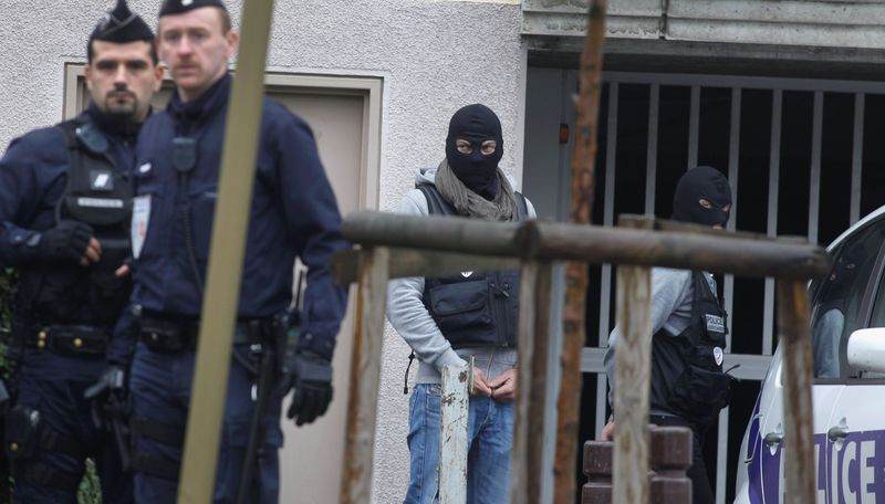 Elite police officers and riot police (left) guard on Wednesday a parking lot in Torcy, east of Paris, where police found bomb-making material after police broke up a suspected terrorist cell last week. Potassium and sulfur were recovered. (Associated Press)
