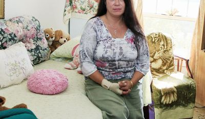 Sherene Julian sits inside her room at the Anna Louise Inn late last month in Cincinnati. A developer wants to buy the 103-year-old home for low-income women and convert it into a boutique hotel. (Associated Press)
