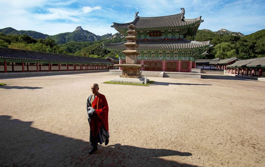 A North Korean Buddhist monk walks on the grounds of the Ryongthong Temple that was restored by the North Korean government near Kaesong, a city where electricity is on for only a few hours every evening.