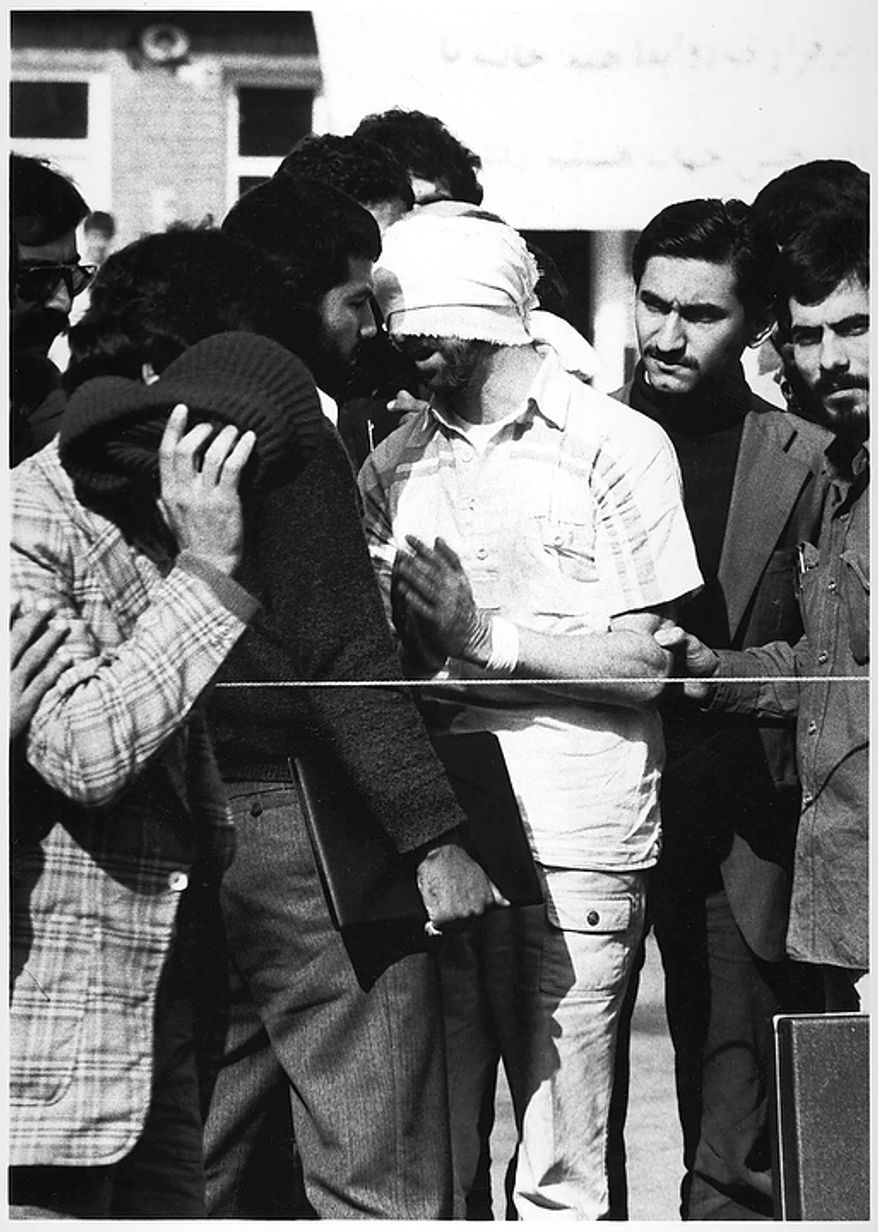 One of 60 U.S. hostages, blindfolded and with his hands bound, is being displayed to the crowd outside the U.S. Embassy in Tehran by Iranian hostage takers. At least 2 former U.S. hostages say they believe the bearded man, far right, is Iranian president-elect Mahmoud Ahmadinejad while several former hostage takers all said they did not think it was Ahmadinejad. A close aide to Ahmadenijad refused to look at the photos or comment on the issue in Teheran Thursday, June 30, 2005.  (AP Photo)