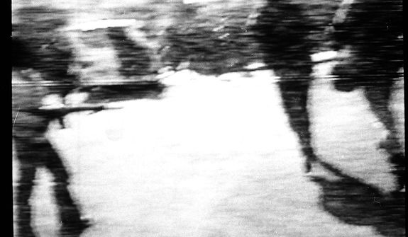 A man carries an assault weapon as others run, Feb. 14, 1979, in Teheran, during the siege on the U.S. Embassy.  Ambassador William Sullivan and 101 other Americans were taken hostage in the attack.  Photo was taken from video monitor showing CBS-TV.  (AP Photo/Suzanne Vlamis)