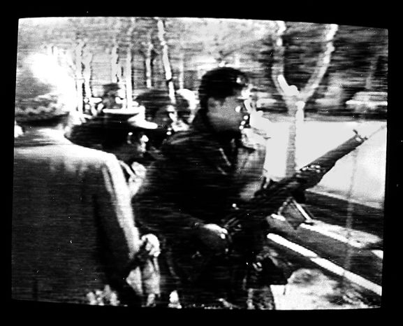 A man carries an assault rifle during the storming of the U.S. Embassy in downtown Teheran, Iran, Feb. 14, 1979.  Ambassador William Sullivan and 101 other Americans were taken hostage. Photo was made from a television monitor showing CBS-TV. (AP Photo/Suzanne Vlamis)