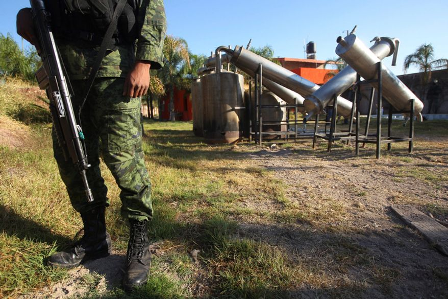 """A soldier stands in what was identified as """"metal reactors"""" on Thursday, Feb. 9, 2012, after a seizure of a large clandestine methamphetamine lab at a ranch in Tlajomulco de Zuniga, on the outskirts of Guadalajara, Mexico. Soldiers made a historic seizure: 15 tons of pure methamphetamine, a haul that could have supplied 13 million doses worth over $4 billion. (AP Photo/Bruno Gonzalez)"""