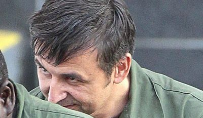 Alexander Fishenko (right), owner of Arc Electronics Inc., hides behind another inmate as they are escorted from the federal courthouse in Houston on Wednesday, Oct. 10, 2012. Mr. Fishenko and seven of his employees are accused of being involved in a scheme to illicitly sell military technology to Russia. (AP Photo/Houston Chronicle, Billy Smith II)