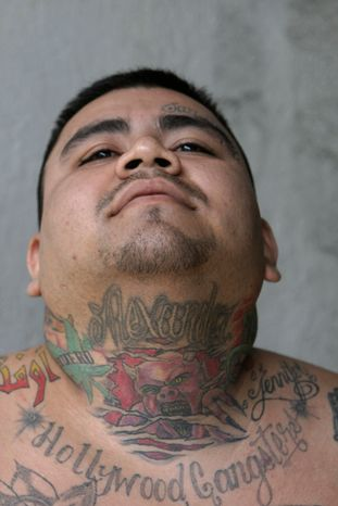 """**FILE** Larios Benitez, aka """"Buda,"""" an alleged member of the Mara Salvatrucha, or MS-13, gang who was arrested on murder and gun possession charges, is shown Aug. 31, 2012, to the press in San Salvador. (Associated Press)"""