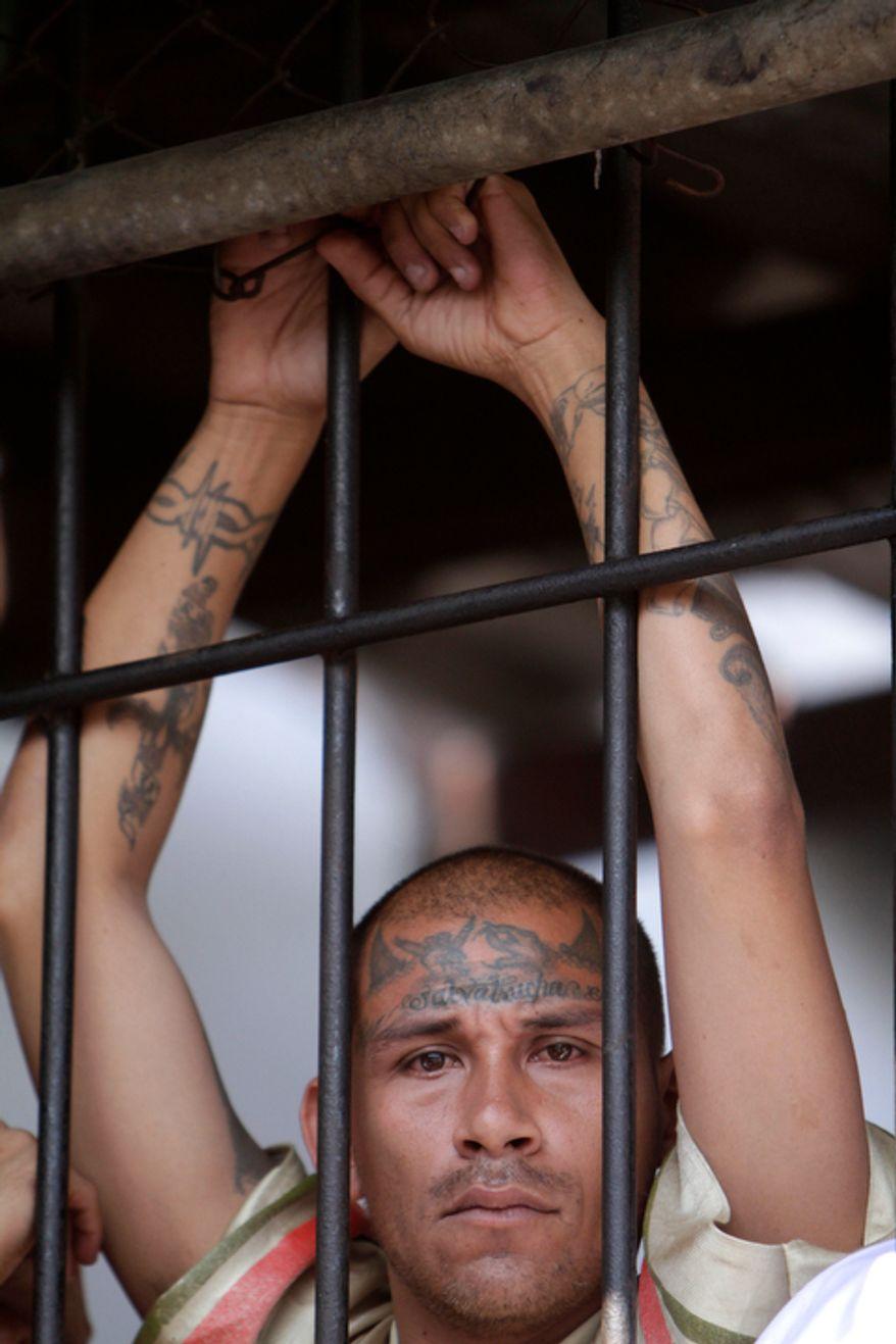 **FILE** A Mara Salvatrucha gang member attends a mass celebrated by Archbishop Luigi Pezzuto, Apostolic Nuncio to El Salvador, and head army and police chaplain Monsignor Fabio Colindres at a prison in Ciudad Barrios, El Salvador, on March 26, 2012. (Associated Press)