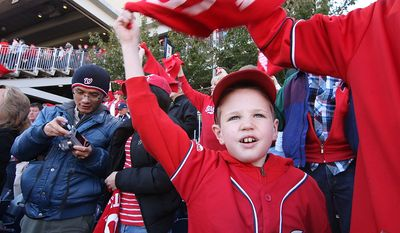 Timmy Sullivan, 8, of Arlington, Va., waves his rally towels during the first inning of Game 4 of the National League Division Series between the Washington Nationals and the St. Louis Cardinals at Nationals Park, Thursday, October 11, 2012. (Craig Bisacre/The Washington Times)