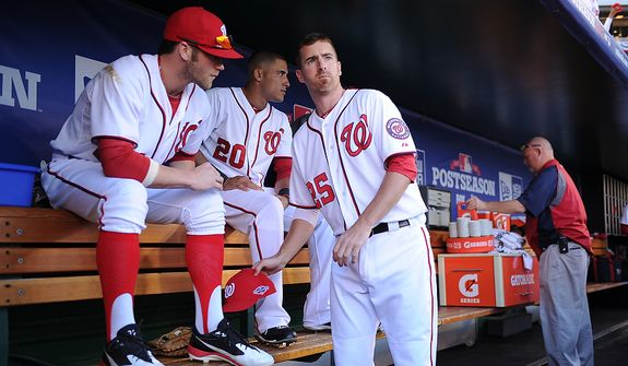 Nationals center fielder Bryce Harper (34),  shortstop Ian Desmond (20) and first baseman Adam LaRoche (25) wait to take the field before Game 4 of the National League Division Series between the Washington Nationals and the St. Louis Cardinals at Nationals Park, Thursday, October 11, 2012. (Andrew Harnik/The Washington Times)