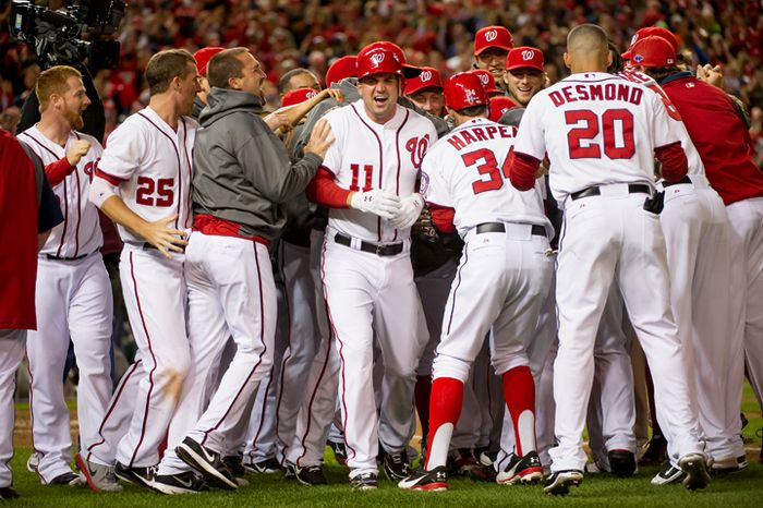 Washington Nationals third baseman Ryan Zimmerman (11), center, and his teammates celebrate as Jayson Werth (28) hits a walk off home run in the bottom of the ninth inning to beat the St. Louis Cardinals 2-1 in game four of the National League Division Series at Nationals Park, Washington, D.C., Thursday, October 11, 2012. (Andrew Harnik/The Washington Times)