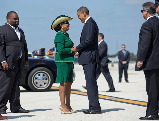 President Obama is greeted Oct. 11, 2012, by Rep. Frederica Wilson (center), Florida Democrat, and Florida state Rep. Dwight Bullard (left) as he steps off of Air Force One at Miami International Airport in Miami. (Associated Press)