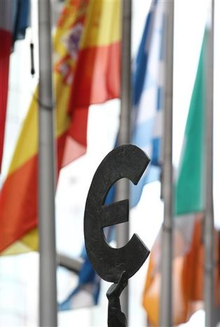 A statue holding the Euro sign is pictured with some flags of EU countries outside the European Parliament building in Brussels, Friday, Oct. 12, 2012. (AP Photo/Yves Logghe) ** FILE **