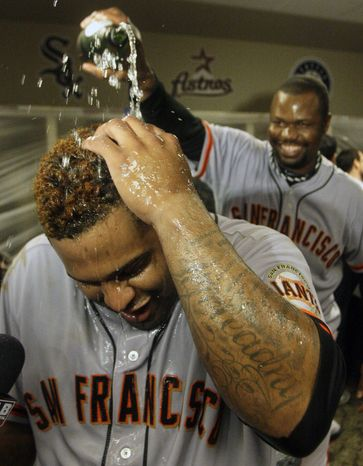 San Francisco Giants' Pablo Sandoval has champagne poured over him while being interviewed in the clubhouse after the Giants defeated the Cincinnati Reds 6-4 in Game 5 of the National League division baseball series, Thursday, Oct. 11, 2012, in Cincinnati. The Giants won the final three games, all in Cincinnati, and advanced to the NL championship series. (AP Photo/David Kohl)