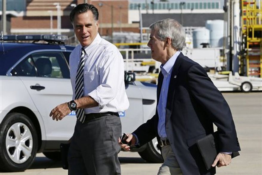 Republican presidential candidate, former Massachusetts Gov. Mitt Romney walks with Sen. Rob Portman, R-Ohio, as he arrives in Richmond, Va., Friday, Oct. 12, 2012. (AP Photo/Charles Dharapak)