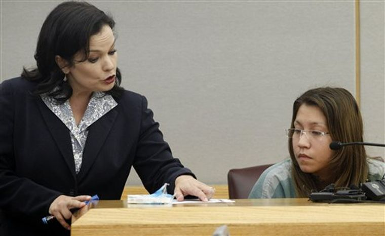 ** FILE ** In a Thursday, Oct. 11, 2012, file photo, prosecutor Eren Price, left, points to a piece of states evidence as she addresses Elizabeth Escalona, 23, during Escalona's sentencing proceedings in Dallas. Escalona was sentenced Friday, Oct. 12, 2012, to 99 years in prison for beating her toddler and gluing the child's hands to a wall. (AP Photo/Tony Gutierrez, File)