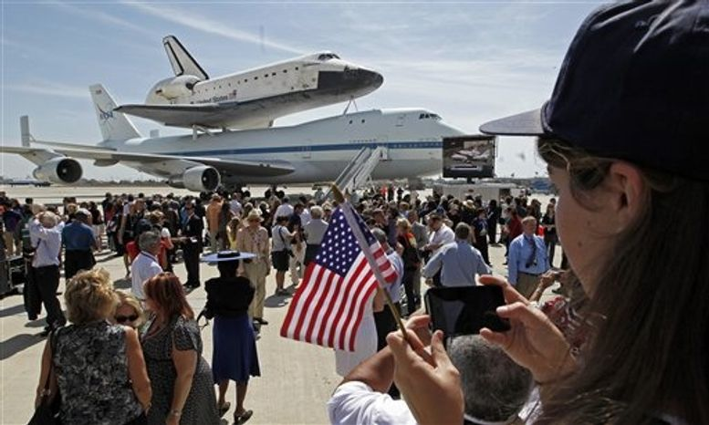 ** FILE ** A girl takes a photo of the Space Shuttle Endeavour aboard a NASA Boeing 747 at the conclusion of its last flight at Los Angeles International Airport Friday, Sept. 21, 2012. Soon, Endeavour will be towed through city streets to its new home at the California Science Center in downtown Los Angeles. (AP Photo/Reed Saxon)