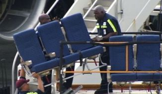 "In this photo provided by WBZ-TV seats from an American Airlines 757 are carried before receiving ""Main Cabin Extra Refurbishment"" Tuesday, Oct. 2, 2012, at Logan International Airport in Boston. American Airlines says passenger seats on a third flight came loose as the plane was airborne Tuesday, and it's continuing to inspect other jets with similar seating. The airline acknowledged Tuesday that seats came loose on a flight last week from Dallas-Fort Worth International Airport to Vail, Colo., and the same thing happened aboard the same plane Monday and a second plane Saturday, according to the airline. (AP Photo/WBZ-TV)"