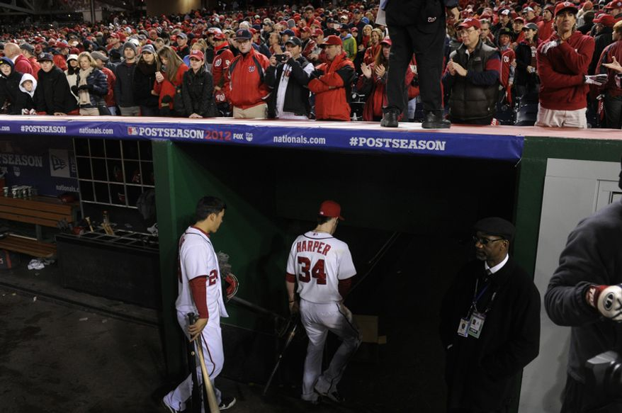 Washington Nationals catcher Kurt Suzuki (24) and Bryce Harper (34) head to the clubhouse after Game 5 of the National League Division Series between the Washington Nationals and the St. Louis Cardinals at Nationals Park, Friday, October 12, 2012. (Preston Keres/Special to The Washington Times)