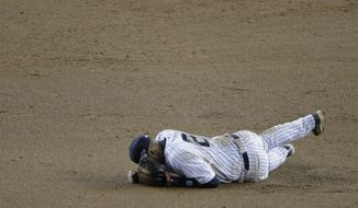 New York Yankees shortstop Derek Jeter reacts after injuring himself in the 12th inning of Game 1 of the American League championship series against the Detroit Tigers early Sunday, Oct. 14, 2012, in New York. (AP Photo/Charlie Riedel)