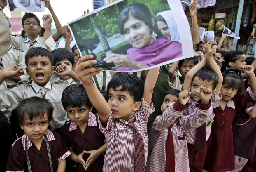 A Pakistani boy holds up a picture of 14-year-old schoolgirl Malala Yousufzai, who was shot on Tuesday, Oct. 9, 2012, by the Taliban for speaking out in support of education for women. The schoolboy and other children are attending a protest in Karachi, Pakistan, on Saturday, Oct. 13, 2012, to condemn the attack. (AP Photo/Fareed Khan)