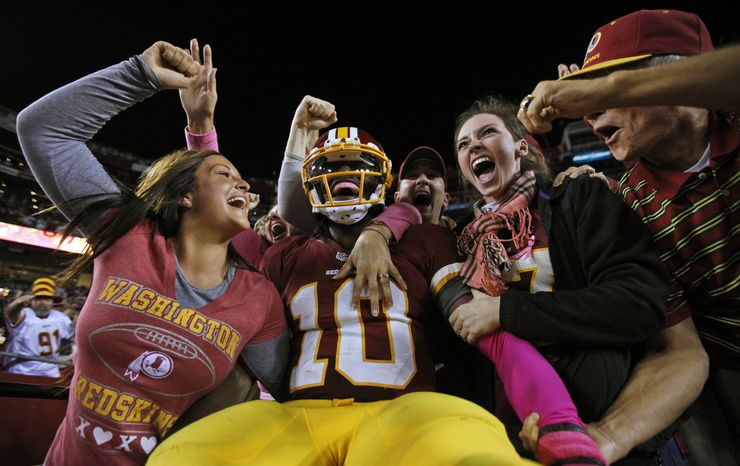 Washington Redskins quarterback Robert Griffin III (10) celebrates with fans after a 76-yard touchdown run during the second half of an NFL football game against the Minnesota Vikings, Sunday, Oct. 14, 2012, in Landover, Md. (AP Photo/Pablo Martinez Monsivais)