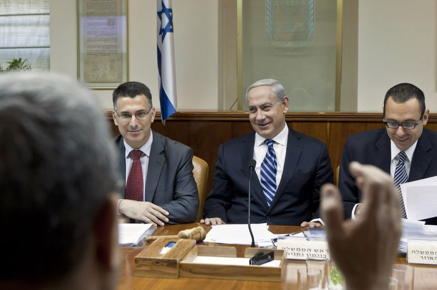 Israeli Prime Minister Benjamin Netanyahu (second from right) laughs as Defense Minister Ehud Barak (with his back to camera) makes a joke that Mr. Netanyahu should give fair time to the opposition in political statements, as the prime minister chairs the weekly Cabinet meeting in his Jerusalem offices on Sunday, Oct. 14, 2012. (AP Photo/Jim Hollander, Pool)