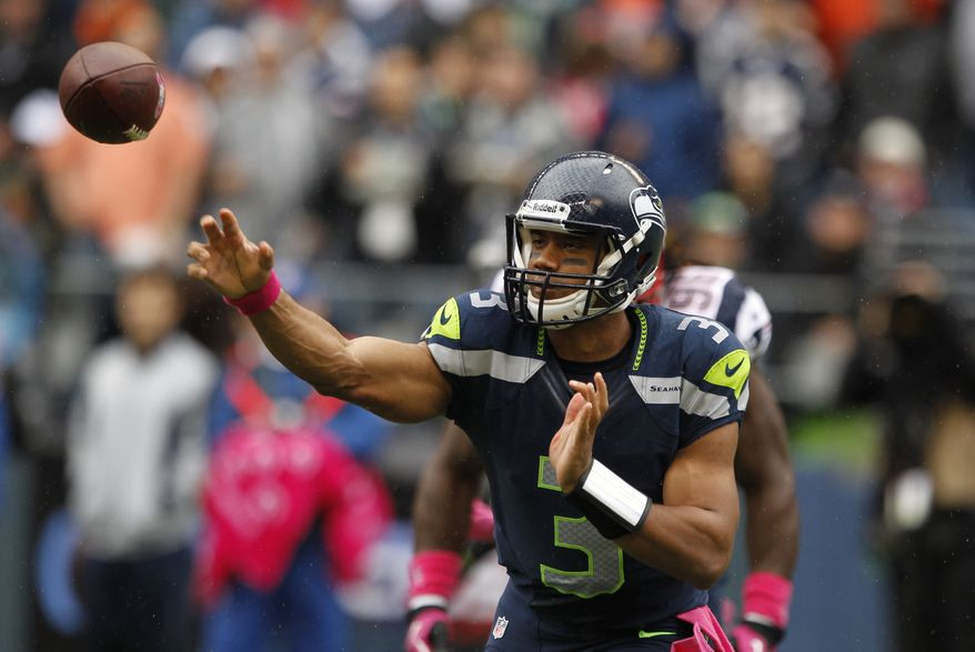 Seattle Seahawks quarterback Russell Wilson passes in the first half of an NFL football game against the New England Patriots, Sunday, Oct. 14, 2012, in Seattle. (AP Photo/Elaine Thompson)