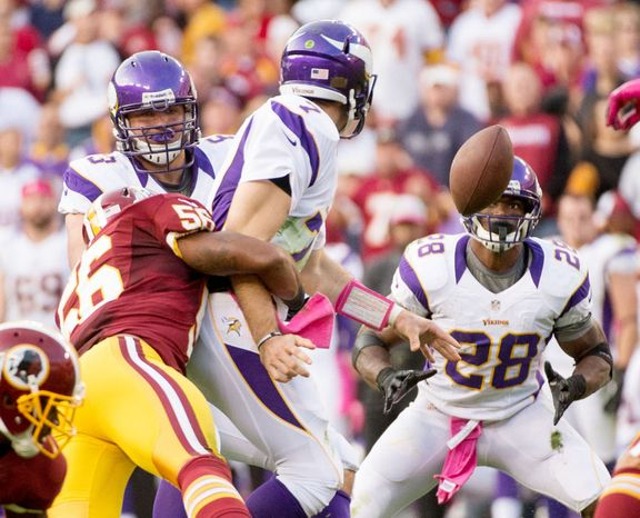 Minnesota Vikings quarterback Christian Ponder (7) flicks the ball out to Minnesota Vikings running back Adrian Peterson (28) as he is hit by Washington Redskins inside linebacker Perry Riley (56) in the second quarter as the Washington Redskins play the Minnesota Vikings. (Andrew Harnik/The Washington Times)