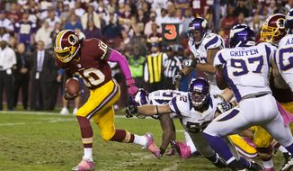 Washington Redskins quarterback Robert Griffin III (10) breaks though tacklers for a 76 yard touchdown in the fourth quarter.  (Craig Bisacre/The Washington Times)