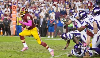 Washington Redskins quarterback Robert Griffin III (10) breaks though tacklers for a 76 yard touchdown in the forth quarter against the Minnesota Vikings, Landover, Md., Sunday, Oct. 14, 2012. (Craig Bisacre/The Washington Times)