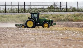 ** FILE ** A tractor works on a cotton field near a border fence that passes through the property in Brownsville, Texas, 2008. (Associated Press)