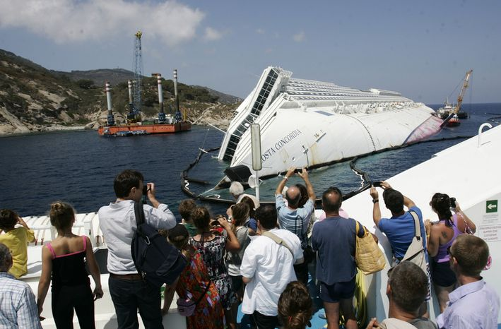 ** FILE ** Tourists take pictures of the Costa Concordia wreckage as they arrive on a ferry to the Giglio Island, Italy, Thursday, July 12, 2012. (AP Photo/Gregorio Borgia)