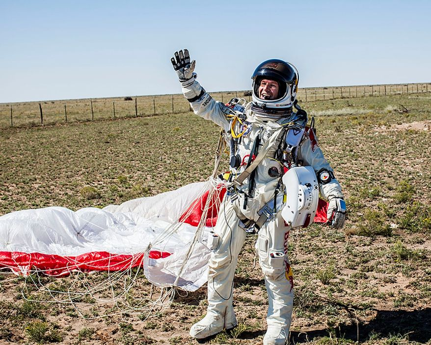 In this photo provided by Red Bull Stratos, pilot Felix Baumgartner of Austria celebrates after successfully completing the final manned flight for Red Bull Stratos in Roswell, N.M., on Oct. 14, 2012. Baumgartner came down safely in the eastern New Mexico desert minutes about nine minutes after jumping from his capsule 128,097 feet, or roughly 24 miles, above Earth. (Associated Press/Red Bull Stratos)